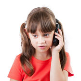 Little girl with a phone on gray background — Stock Photo