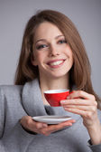 Cute girl holding a cup of coffee — Stock Photo