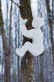Schittering van de sneeuw man kruipen op een boom — Stockfoto