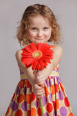 Happy little girl gives a flower to someone — Stock Photo