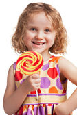 Happy little girl with a lollipop — Stock Photo