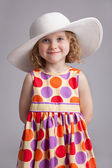 Beautiful little girl in a wide-brimmed hat — Stock Photo