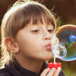 Little girl inflates a big bubble - Stock Photo