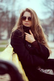 Elegant woman in sunglasses on the bench — Stock Photo