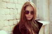 Fashion model in a black coat and sunglasses — Stock Photo