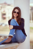 Charming woman in glasses and blue jeans — Stock Photo