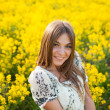 Stock Photo: Beautiful womamong yellow flowers in field