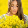 Stock Photo: Young womwith bouquet of yellow wildflowers