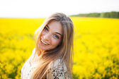 Beautiful young woman of yellow wildflowers — Stock Photo