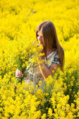 Girl in the field of yellow flowers — Stock Photo