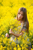 Beautiful girl with a bouquet in the field — Stock Photo
