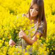 Stock Photo: Girl gathers bouquet of yellow wildflowers