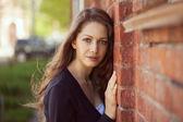 Beautiful woman near a brick wall — Stock Photo