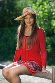 Beautiful girl in a red dress and a hat — Stock Photo