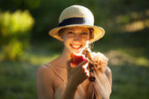 Happy woman in hat eating apple — Stock Photo