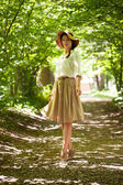 Beautiful elegant woman in a hat among green foliage — Stock Photo