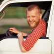 Driver in a red shirt while driving — Stock Photo #28288693