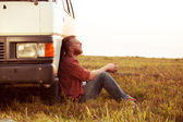 Driver resting in a field near his car — Stock Photo