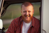 Cheerful red-bearded man in a plaid shirt — Stock Photo