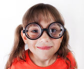 Funny little girl in round glasses — Stock Photo