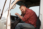 Somewhat puzzled bearded driver in the cab — Stock Photo