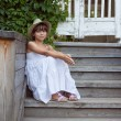 Cute little girl is sitting — Stock Photo