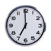 Round office clock shows seven o'clock — Stock Photo