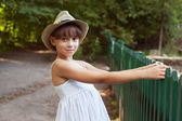 Girl in the hat next to a fence — Stock Photo