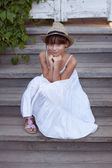 Happy girl in a hat and dress — Stock Photo