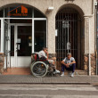 Disabled person in a wheelchair on a city street — Stock Photo