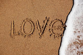 Word love on the beach is washed off with water — Stock Photo