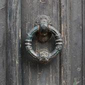 Old doorhandle on green wooden door — Stock Photo