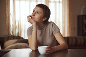 Dreamy girl sitting with a cup of coffee — Stock Photo