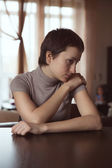 Sad woman sitting with hands clasped — Stock Photo