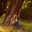 Romantic young woman sitting under a tree — Stock Photo