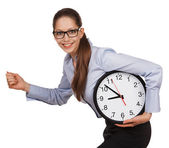 Girl with glasses runs with a clock in his hands — Stock Photo