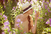Beautiful woman enjoying the scent of wildflowers — Stock Photo