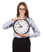 Smiling young woman holding a clock — Foto Stock