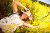Happy woman lying among yellow wildflowers — Stock Photo