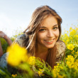 Happy girl lies among yellow wildflowers — Stock Photo #40714499