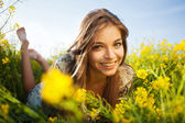 Happy girl lies among yellow wildflowers — Stock Photo