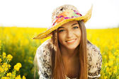 Happy woman in a hat of wildflowers — Stock Photo