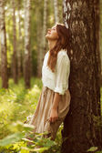 Woman leaning against birch and resting — Stock Photo