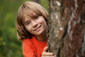 Boy in red T-shirt peeking out from behind a tree trunk — Stock Photo