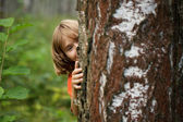 Boy peeking out from behind a tree trunk — Stock Photo