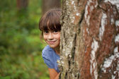 Little girl peeking out from behind a tree trunk — Stock Photo