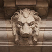 Muzzle ferocious lion carved in stone — Stock Photo