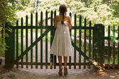 Girl standing on tiptoes and looking over the fence — Stock Photo
