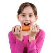 Happy girl eating a large carrot — Stock Photo