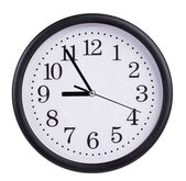 Round wall clock shows five to nine — Stock Photo